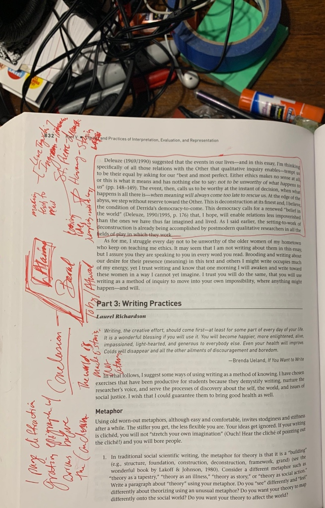 Image of a page in a textbook. In the wide, blank margin, there is a mess of words and terms and lines in red ink. The writer was obviously trying to organize their thoughts on the book page. Above the book is a desk with a mess of objects--tape, glue stick, earphones, paper, stickers, cords, pens, post-its and more.