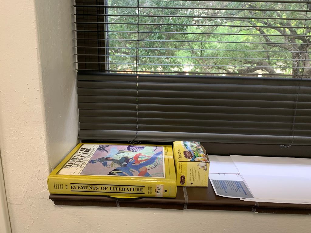 A yellow Elements of Literature textbook and a yellow box of Celestial brand tea sit on a brown tile window ledge in front of brown blinds partially open to show trees through the window.